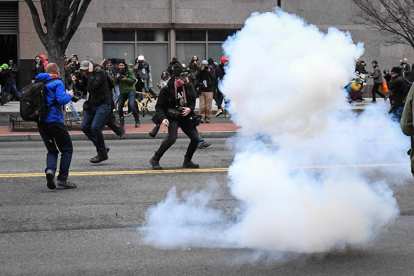 Protesters and journalists scramble as stun grenades are deployed by police during a protest near the inauguration of President Donald Trump in Washington, DC, U.S., January 20, 2017.