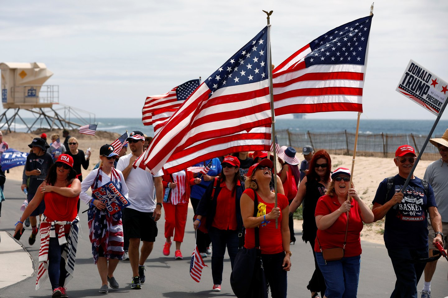 Pro-Trump rally participants carry flags during the Southern California Make America Great Again march in support of President Trump, the military and first responders at Bolsa Chica State Beach in Huntington Beach, California, U.S. March 25, 2017.