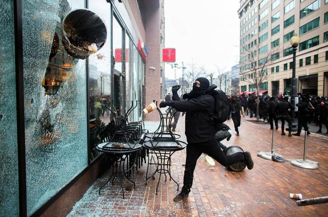 demonstrator smashes a Starbucks window using a trash can